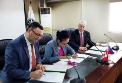 CBIE Vice President for International Partnerships Basel Alashi and CHED Chairperson Patricia Licuanan sign the contract for the implementation of various education programs in Canada, with Canadian Ambassador to the Philippines John Holmes looking on.